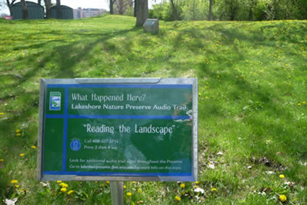 A small green sign marks the location of an Audio Trail station at the Willow Creek Woods burial mounds.