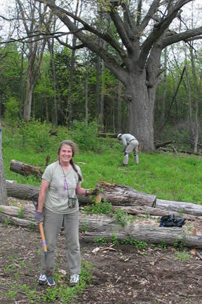 Volunteer Glenda Denniston holds a tool and poses in front of a big oak tree.