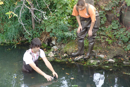A student wearing waders stands in Willow Creek up to his waist and collects a water sample while another student in waders watches from the shore.