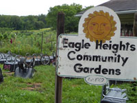 "A sign with a smiling sun on it reads, ""Eagle Heights Community Gardens est. 1962""."