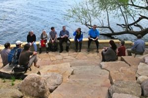 A dozen members of the Preserve Committee sit on the steps on the tip of Picnic Point for a meeting.