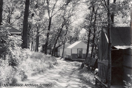 Canvas tents line a dirt path under a forest canopy in the Camp Gallistella Tent Colony.