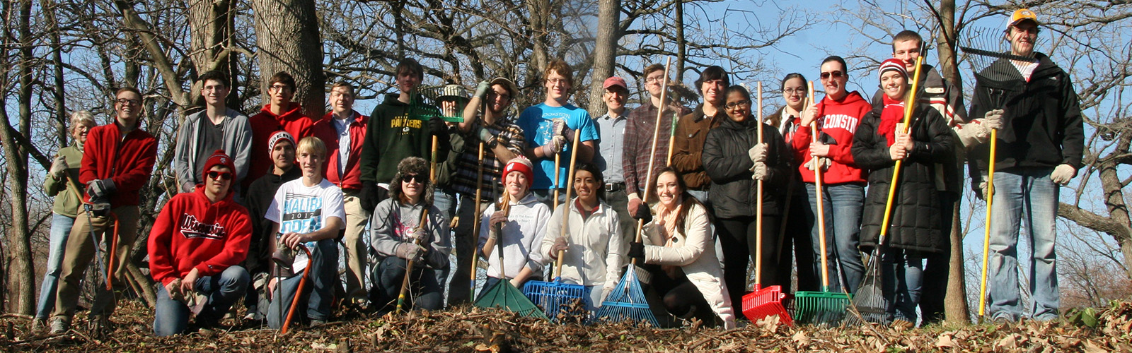 A large group of volunteers pose for a photo holding rakes and other tools.
