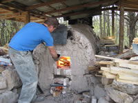 A student adds wood to the fire inside the anagama kiln.