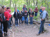 A group of students stand around their soils professor at a soil pit in Bill's Woods.