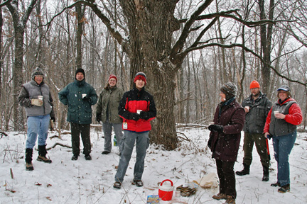 Seven volunteers bundled up in winter clothes stand under a large oak tree holding cups of hot chocolate while it snows.