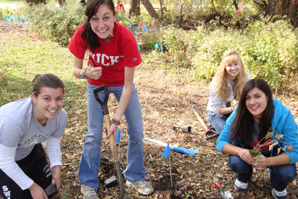 Four smiling student volunteers plant wildflowers along the Howard Temin Lakeshore Path.