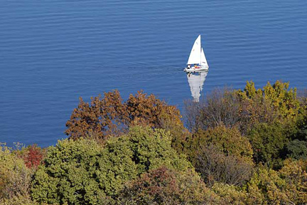 A sailboat on Lake Mendota near the wooded shoreline of the UW-Madison campus is pictured in an aerial view during autumn.