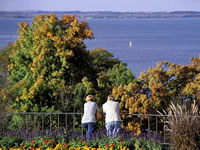 Two adults take in the fall colors and the view of Lake Mendota from the Observatory Hill overlook.