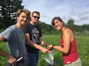 Three college students standing together. All are looking t the camera. One is holding a plastic bag and another is putting a soil sample in it.